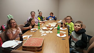 Students eating pizza with the principal
