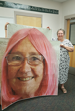 Staff member poses with a large poster of Principal Debbie Mulder in a pink wig