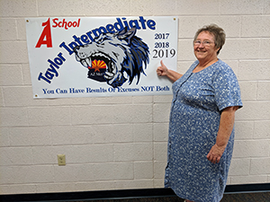 Principal next to sign with A School Taylor Intermediate 2017, 2018, 2019 - You can have results or excuses NOT both