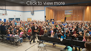 Click to view more. Taylor Elementary and Taylor Intermediate students raise their hands to participate in Anthony the Magic's presentation.