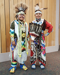 Two students dressed in Native American attire pose and smile together