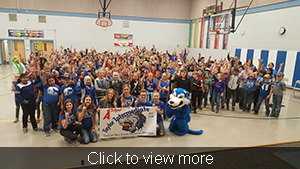 Student body, student council and the mascot pose together with the A School banner