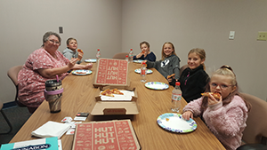Five students eat pizza with the principal