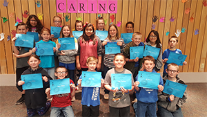 Students of the Month pose together with their certificates