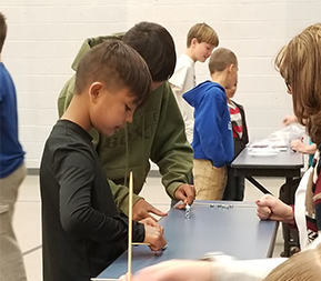 Students participate in an activity using forks