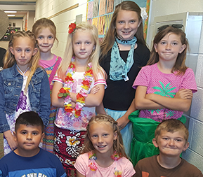 Students pose in Hawaiian outfits