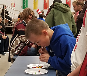 Student participates in a project using Skittles, a straw and a paper plate