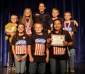 Students pose with DARE certificates and a police officer