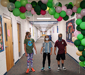Three Taylor Intermediate students in the jungle themed hallway wearing a mask