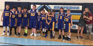 Basketball team poses together in a gym