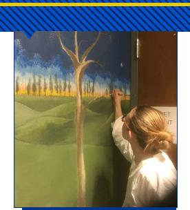 Artist Lisa Hoffman painting wall