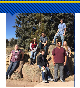 Students sitting on a rock formation