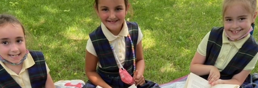 Three students outside posing for a picture with green face masks
