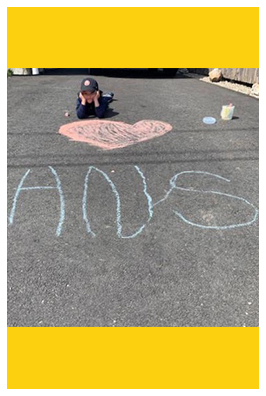 Student laying next to HNS chalk drawing outside