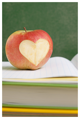 An apple with heart-shaped bite on top of books
