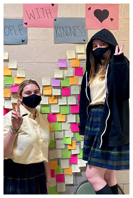 students giving peace signs in front of wall of post-its