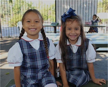 two little girls in school uniforms