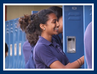 Female student laughs as she opens a locker
