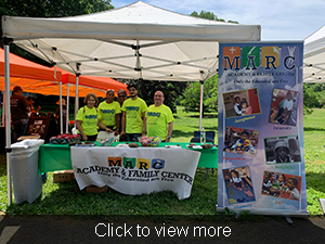 Click to view more. Staff members pose in front of the MARC Academy and Family Center booth.