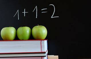 Three apples sit on top of books and 1+1=2 written on a blackboard