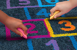 Students draw hopscotch pattern with chalk