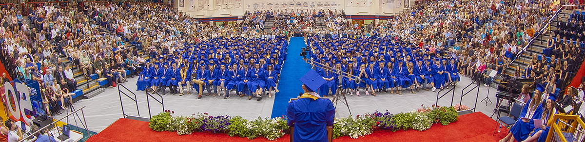 Wide view of graduation speaker giving a speech to graduates and their families