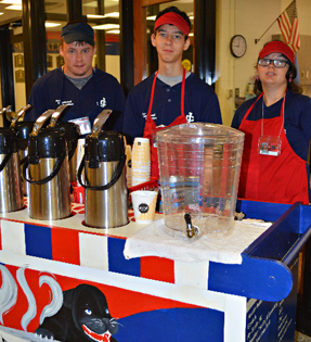 three students working at a coffee cart