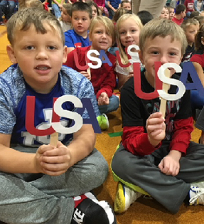 students holding red, white and blue USA signs