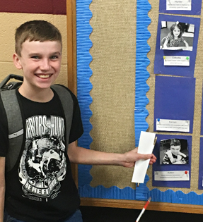 young boy pointing to a picture on bulletin board