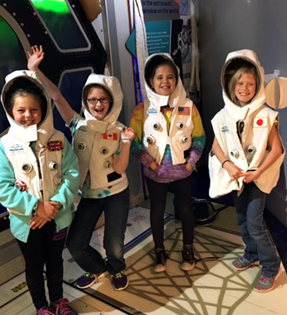 four students dressed as astronauts