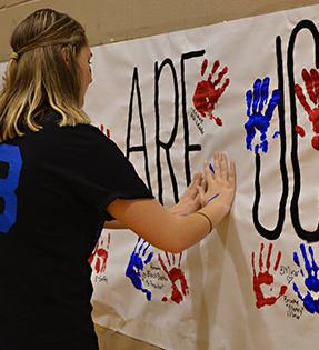 Student making paint handprint on banner