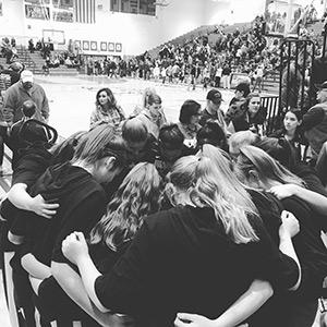girls basketball team in a huddle