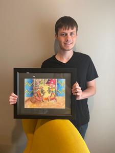 Kayden Gresham holding up his art
