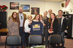 Sydney Campbell holding a Marian University t-shirt and surrounded by family and friends