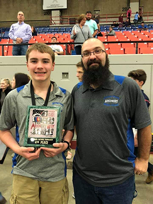 Aron Spencer poses with his award and a coach