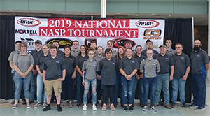 Archery team members and coaches pose in front of a 2019 National NASP Tournament sign
