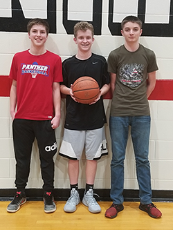 Three male students pose together with a basketball