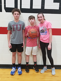 Two male students and a female student pose together with a basketball