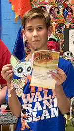 Male student holds up his winning coloring