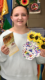 Female student holds up her winning coloring with sunflowers