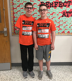 two students in matching orange shirts that say dusk til dawn