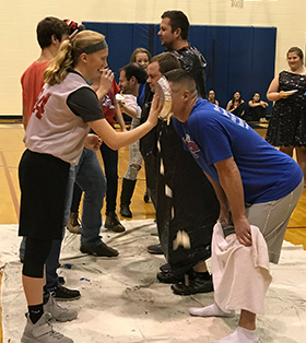 students throwing pies in faculty's faces