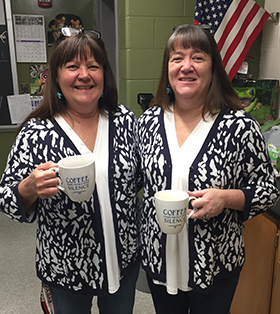 two teachers in matching sweaters holding coffee mugs