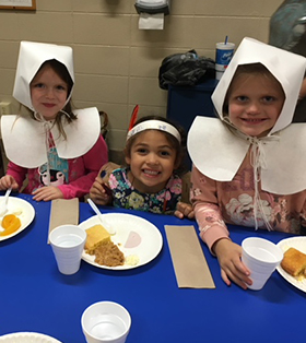 three elementary students dressed up as pilgrims