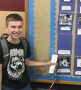 boy pointing to bulletin board