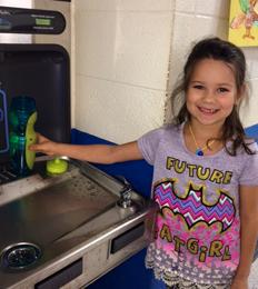 little girl filling her water bottle