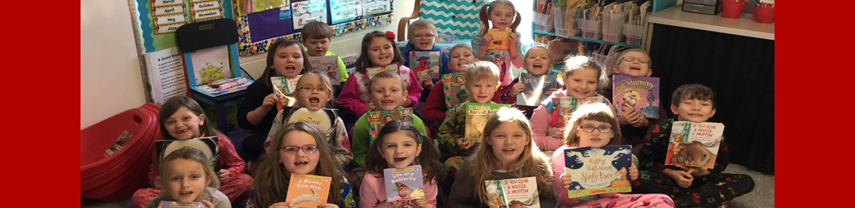 students smiling holding their new books