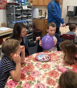 Students participating in a science activity with a balloon