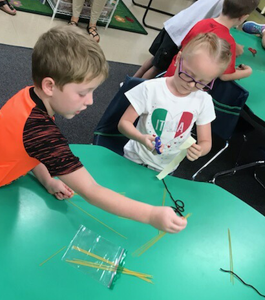 two students participating in an activity with string and sticks