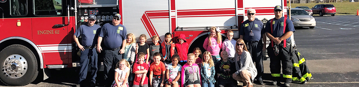 North Vernon Elementary School students pose in front of a firetruck with firefighters